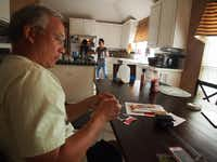 Mark Roberson manages apps on his phone May 18 while his wife Marcie pours herself a cup of coffee. The family lives in Stafford Estates near the north shore of Grapevine Lake. The neighborhoods in that area were found to be the best for suburbs in a recent study by The Dallas Morning News.