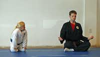 Abigail Allen, 6, of Richardson, watches Allen Butler (right), 20, of Lewisville, as he meditates at North Dallas Martial Arts in Richardson.  Butler is autistic and was testing to receive his black belt.(Stewart F. House - Special Contributor)