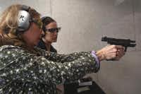 Janie Brewer, left, shows her daughter Sarah Delapaz technique during Ladies Night at the Frisco Gun Club on February 19, 2014 in Frisco. The club offers half-off to women on Wednesday evenings.(Sarah Hoffman - Staff Photographer)