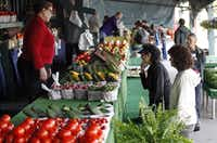 Fatima Amaroufi (left) of Allen, waits on Debbie Engell (right) of Plano and Toni Nesmith of Plano as she makes up her mind at the the Collin County Farmers Market in Plano which was having their opening day on Saturday, April 20, 2013.(Stewart F. House - Special Contributor)