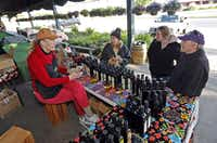 Karen Henry (left) of Dallas, sells olive oil from her ranch in Carrizo Springs to Plano residents Dena Moore, Shannon Matson (second from right) and Tom Moore (right) at the the Collin County Farmers Market in Plano which was having their opening day on Saturday, April 20, 2013.(Stewart F. House - Special Contributor)