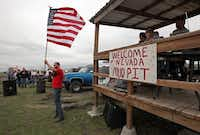 Robert Stephens of Rowlett volunteered to hold the U.S. flag during the national anthem prior to the mud-bogging races at The Pits in Nevada, Texas.(Stewart F. House - Special Contributor)
