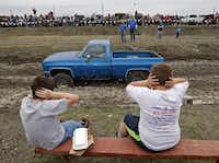Wylie residents Kadon Couch (left), 8, and Jacob Swartz, 7, cover their ears at the sound of the roaring engine of a vehicle competing at the Nevada Mud Pits March 22.(Photos by <TypographyTag16>Stewart F. House</TypographyTag16> -  special contributor )