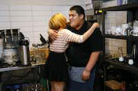 Host manager Keisha Whaley (left) hugs intern Thomas Guandique as they start their evening shift at Café Momentum.(Kye R. Lee - Staff Photographer)