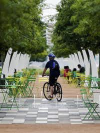 A cyclist rides along a path at Klyde Warren Park on Monday.( Photo by BRANDON WADE  -  DMN special contributor )