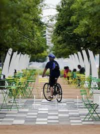 A cyclist rides along a path at Klyde Warren Park on Monday.Photo by BRANDON WADE  -  DMN special contributor