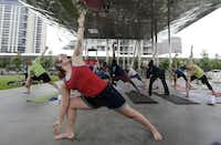 """Yoga instructor Mandee Carr leads a class at Klyde Warren Park during Uptown Ciclovía. The name """"ciclovía"""" means bicycle path and comes from the gathering's origins in Bogotá, Colombia, in the 1970s, with the city shutting down miles of road to automobile traffic each Sunday.Photo by BRANDON WADE - DMN special contributor"""