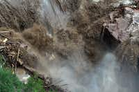 This aerial photo shows a raging waterfall destroying a bridge along Highway 34 toward Estes Park, Colo. as flooding continues to devastate the Front Range and thousands are forced to evacuate with an unconfirmed number of structures destroyed Friday, Sept. 13, 2013.