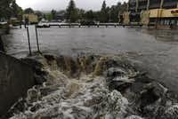 A heavy flow of water pours out of a parking lot on E. Elkhorn Ave. overwhelming a culvert heading under the roadway. As a steady rain continues to fall, the town of Estes Park, Colo., begins Sunday Sept. 15, 2013 to clean up the flooded downtown streets and stores that are popular for visitors.