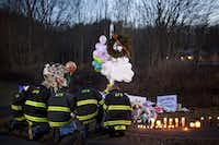 FILE -- Firefighters pay their respects to the victims of the shooting at Sandy Hook Elementary School at a makeshift memorial at the entrance to the school in Newtown, Conn., Dec. 15, 2012. Newtown, still grieving after the elementary massacre, is wrestling with the question of how long to let public memorials stand. (Fred R. Conrad/The New York Times)(MARCUS YAM - NYT)