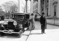 In this photo released by the Vermont Historical Society, President Calvin Coolidge is seen next to one of his Lincoln Town Cars in Washington, D.C. in 1924.