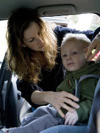 Anita Lavine buckles son Owen Turcotte, who is about to turn 2, into his car seat before heading off to school in Seattle, Friday, April 25, 2008. Lavine says she generally does not leave her children in the car alone, but has done it once or twice outside a dry cleaner with the car in sight.