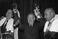"CBS newscaster Walter Cronkite holds up the hands of Republican National Committee Chairman George Bush, left, and Democratic National Committee Chairman Robert Strauss during Thursday's Circus Saints and Sinners Club luncheon in Washington, March 8, 1974. Bush and Strauss put on the gloves for what was called the ""Battle of the Century."" Both were delcared winners by Cronkite.( ASSOCIATED PRESS )"