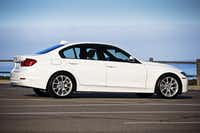 The 2013 BMW 320i, equipped with a four-cylinder engine, weighs about 3,300 pounds -- 200 or so less than a loaded six-cylinder car.