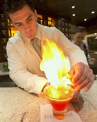 One of the mixologists at the cocktail pharmacy-themed Alchemy Bar on the Carnival Sunshine, uses a flame as the finishing touch to one of the loungeaïs custom cocktails.