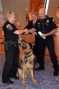Wylie Police Deparment's K-9, Caro, looks up to his partner, Officer Brenda Martin, as she shakes hands with Police Chief John Duscio. Mayor Eric Hogue, back, read a proclamation in honor of Caro, who is retiring after five years of service on the force.( Photo submitted by CRAIG KELLY )