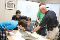 Michael Mammadov (left), 13, Jorge Garcia, 12, Brandon Prewitt, 12, and John Crisford, 13, examine a piece of carpet for evidence under the instruction of Dustin Bartram, Carrollton Police Department crime scene investigator, during the Junior Police Academy. The activity was one of several hands-on learning opportunities included in the program.