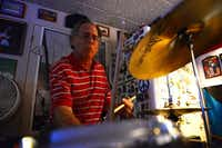 Drummer David Michnoff of The Catdaddies rehearses in the converted garage of Mark Sales — a cramped, converted man cave with Beatles posters and neon  beer signs in Lake Highlands.(  Rose Baca  - neighborsgo staff photographer)