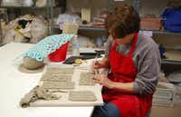 Marcia Taylor works with slabs of clay during a ceramics class at the Creative Arts Center of Dallas. Taylor started taking classes at the center when her sons bought her a class last Christmas.Staff photo by ANANDA BOARDMAN