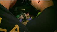 Firefighters use a special mask to administer oxygen to a dog rescued from a burning home in Dallas.( NBC5 screencap )