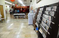 Racks of Chinese newspapers line the walls of the Dallas Chinese Community Center while a group of women in the background move slowly to music during a tai chi dance class.(Rose Baca)