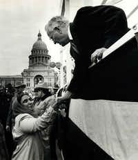 Gov. Bill Clements shook hands with a supporter from the reviewing stand during the Inaugural Parade in Austin on Jan. 20, 1987.