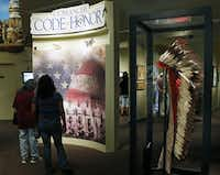 People walk through an exhibit about the Comanche Code Talkers at the Comanche National Museum & Cultural Center in Lawton, Okla, Thursday, Sept. 26, 2013.