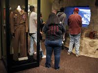 A World War II uniform with the bandolero worn by Comanche Code Talker Charles Chibbity is on display in an exhibit about the code takers at the Comanche National Museum & Cultural Center in Lawton, Okla, Thursday, Sept. 26, 2013. At right, people watch a video on the D-Day invasion at Normandy.