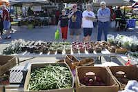 Customers eye Stacy Finley's display of vegetables during the Coppell Farmers Market.Matthew Busch  -  Staff Photographer