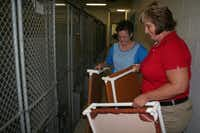 Rusty Lemley (background) and Lancaster Animal Shelter supervisor Kim Pekofske put beds in kennels for the dogs.