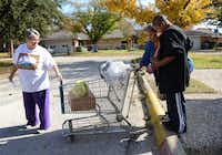 Volunteer Mary MacDonald (left) helps Linda Wooten and her grandson LaDarrian Wooten with their donated grocery items at Oak Cliff Churches for Emergency Aid on Nov. 19 in Dallas. The agency is a collective effort among 25 area churches to offer food and referrals for jobs and clothing each weekday morning to Oak Cliff residents in need.