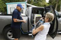 Carol Merritt (right) hugs one of her rescue dogs before saying good-bye and handing it off to Terry Ratliff, a volunteer who will transport to Dallas/Fort Worth International Airport. The dog will be flown to Salem, Mass., to adoption centers, where many say the stray dogs are more likely to be adopted.( David Woo  -  Staff Photographer )