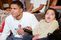 Caleb Evans, 17, watches Monday Night Football with his brother Nathaniel, 8, at their home in Mansfield. While doctors gave no official diagnosis for Nathaniel's disability, which occurred when he was only a few weeks old and rolled over in his sleep and stopped breathing for an unknown amount of time, they say it most closely resembles cerebral palsy.(Brandon Wade - Special Contributor)