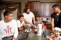 Caleb Evans (left), 17, and his siblings Simeon, 13, Trey, 27, Titus, 10, Naomi, 6, and Jerod, 21, have dinner while watching Monday Night Football at their home in Mansfield.(Brandon Wade - Special Contributor)