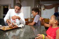 Bishop Dunne senior quarterback Caleb Evans, 17, cuts off pieces of a baked chicken for his younger siblings Titus, 10, and Naomi, 6, while watching an NFL Monday Night Football game at their home in Mansfield.( Brandon Wade  -  Special Contributor )