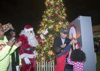DeSoto Mayor Carl Sherman, his grandson, Carl Sherman III, and Kendall Morris flip the switch during the tree lighting ceremony in DeSoto Dec. 5, 2014.( Rex C. Curry  -  Special Contributor )