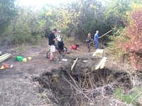 Volunteers from the Dallas Off Road Bicycle Association work around a sink hole created by rain at Cedar Hill State Park.( Photo submitted by MALEA JAFFE )