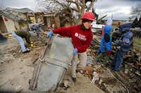 Team Rubicon volunteer Molly Gayden of Fort Worth hauls a piece of garage door to the curb as they clean up the tornado ravaged home on Mesa Wood Drive in Glenn Heights.(Tom Fox - Staff Photographer)