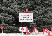 A protester dressed as a Canadian Mountie accusing Sen. Ted Cruz of liking Nickelback, an oft-maligned Canadian grunge band. He and two others in Mountie costumes also handed out copies of Cruz's Canadian birth certificate outside Cruz's rally with conservative talk show host Glenn Beck on Saturday in Ankeny, Iowa. (staff/Todd J. Gillman)