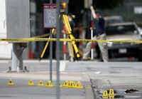 Evidence markers on seen on a sidewalk in front of Dallas police headquarters as members of the FBI evidence response team, rear, investigate an intersection in front of the building Saturday June 13, 2015, in Dallas. A police sniper shot a cornered suspect in an overnight attack on the Dallas Police Department's headquarters, and authorities were checking Saturday to see if he was alive or dead. (AP Photo/Tony Gutierrez)