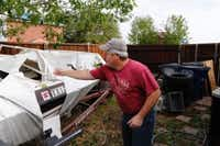 Brian Swinney inspects the damage to his boat at his home after Monday's storm in the 900 block of Heatherwood Street in Wylie on Tuesday. (David Woo/Staff Photographer)
