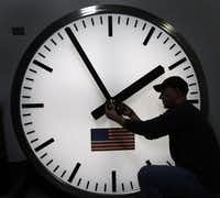 FILE - Dave LeMote uses an allen wrench to adjust hands on a stainless steel tower clock at Electric Time Company, Inc. in Medfield, Mass., in this March 7, 2014 file photo. (AP Photo/Elise Amendola, File)