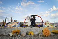 Surrounded by fresh marigolds, participants in the annual Dia De Los Muertos celebration in Terlinga Ghost Town pose between two of the cemetery's altars during the annual Nov. 2 celebration.( Robert W. Hart  -  Special Contributor )