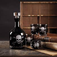 PICK YOUR POISON: Twos Company's Skellington Skull and Crossbones smoked glass decanter and double old-fashioned glasses hit on a hot year-round trend -- decorating with Jolly Roger motifs. Decanter, $75 glasses, $22.50 each. The Corner Market, 3426 Greenville Ave., Dallas.