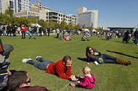 Matt Baker (left) plays with his 11-month-old daughter, Kate Baker, during opening ceremonies at Klyde Warren Park on Oct. 27. The five-acre park sits atop Woodall Rodgers Freeway, connecting downtown, Uptown and the Arts District.