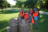 Nio Knight (center) reads the GPS coordinates for a cluster of trash cans at Winfrey Point while Michael Thomas (left) and Trevlan MacGregor (right) look on. The boys are members of Boy Scout Troop 42, which is based at St. Andrew's Presbyterian Church.( Staff photo by ANANDA BOARDMAN )