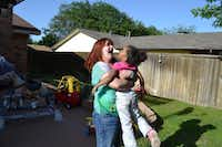 Kimmy picks up her 4-year-old daughter for a kiss while playing in the backyard before dinner.(Staff photos by NANETTE LIGHT - neighborsgo)
