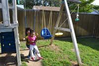 Kimmy's daughters swing in the backyard at Emily's Place.(Staff photo by NANETTE LIGHT - neighborsgo)
