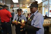 Deanna Hall (right) reads off orders handed from waitress Rena Taylor (center) to manager Tracy Douglas. DOORS helped to connect Hall to a job in May at Waffle House on West Northwest Highway. An Illinois native, Hall was released from a Georgia prison on probation in March 2013, when she moved to Dallas to live with her father. She served four years of a 15-year sentence on an aggravated assault charge.(Staff photo by NANETTE LIGHT -  neighborsgo  )