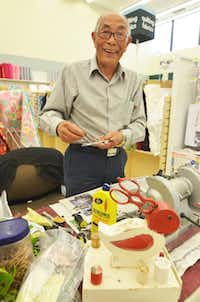 George Katsumoto of Grand Prairie sharpens scissors at the Jo-Ann store on Preston Road in Dallas one day a week. In the foreground is a pair of vintage red scissors in a bird-shaped sewing caddy.